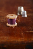 Real old reels spoon treads with needle and thimble. On old wooden table Stock Photos