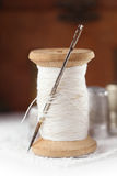Real old reels spoons treads with needle and thimble on white wo. Oden table Royalty Free Stock Images