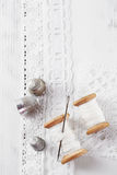 Real old reels spoons treads with needle and thimble on white wo. Oden table Stock Image