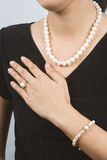 Real pearl Women jewelry shown on the woman in black dresses. Royalty Free Stock Image