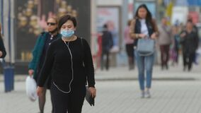 Real People Walk City Street. Woman in Respiratory Mask. Corona Virus Public