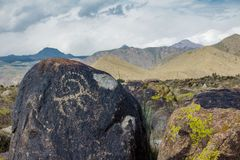 Real petroglyphs on natural stone found in the steppe, on a blurred background of beautiful mountains. Real petroglyphs on natural stone found in the steppe, on royalty free stock image