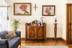 Real photo of an antique cabinet with porcelain decorations, paintings with roses and blue sofa in a living room interior royalty free stock photography