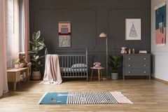 Real photo of a baby crib in a grey child`s room interior, next. To a cupboards, lamp and plants royalty free stock photography