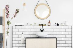 Real photo of a bathroom interior with a round mirror, sink with black faucet and pink flower. Concept royalty free stock photography