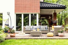 Real photo of a beautiful terrace with garden furniture, plants. And swing stock images