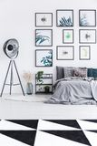 Real photo of a bed standing next to a shelf with plants and a b. Lack lamp in a bedroom interior with black and white rug and wall full of posters stock image