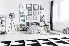 Real photo of a black and white bedroom with a bed standing between a lamp and a chair and next to a wall with plants paintings royalty free stock photos