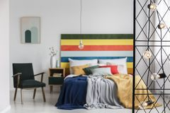 Real photo of blurred bedroom interior with green, retro armchair and colorful bed with rainbow bedhead behind black, metal screen. With lights stock photo