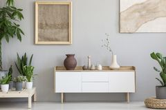 Real photo of a botanic living room interior with burlap artwork. On the gray wall and white cupboard surrounded by plants stock photos