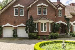Real photo of a brick house with a bay window, garages and round. Garden in front of the entrance concept stock photos