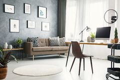 Real photo of a bright home office interior with a sofa, graphic