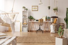Bright room interior with hammock, fresh plants and home office corner with wooden desk, chair and decor. Real photo of bright room interior with hammock, fresh stock image