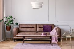Real photo of brown leather sofa with violet cushion and pastel pink blanket standing in light grey sitting room interior with Mon stock photo