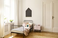 Child bedroom interior with a single bed, window and blackboard on a wall. Real photo of a child bedroom interior with a single bed, bedside table, window and royalty free stock image