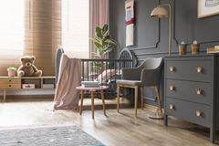 Real photo of a cot standing next to an armchair, lamp and cupboard in dark and classic baby room interior stock photos