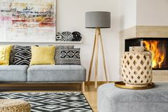Real photo of a couch with pillows standing next to a lamp and b. Ehind a patterned rug and a pouf with wooden basket in living room interior with painting and stock photo