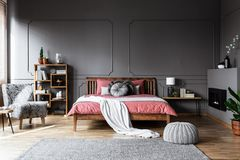 Real photo of a cozy bedroom interior with wooden bed in the mid. Dle, fireplace on the right and gray, patterned armchair on the left royalty free stock photos