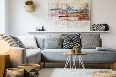 Real photo of a cozy couch with cushions standing behind a small. Table and in front of a shelf with a painting in boho living room interior with baskets and royalty free stock photo
