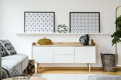 Real photo of a cupboard standing between a couch and a basket,. A shelf with posters above in living room interior royalty free stock photos