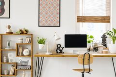 Real photo of a desk with a computer screen, lamp and ornaments. Standing with a chair next to a rack in a work room with posters on a wall and window with stock photos