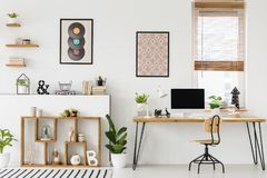 Real photo of a desk with a mockup computer screen, ornaments an. Real photo of a desk with a computer screen standing with a chair next to shelves with royalty free stock photos