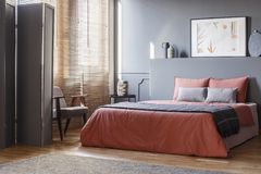 Real photo of elegant bedroom interior with black walls, brown b. Linds and orange sheets on gray bed stock photo