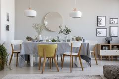 Elegant dining room interior with a laid table, chairs, mirror on a wall and lamps. Real photo of an elegant dining room interior with a laid table, chairs stock image