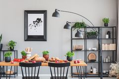 Real photo of an elegant daily room interior with a black shelf, lamp and dining table with herbs, bread and vegetables royalty free stock images