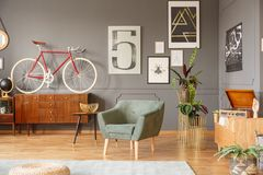 Real photo of a green armchair on wooden floor, old-fashioned si. Deboards with red bike and gramophone on them and other hipster furniture in living room royalty free stock photography