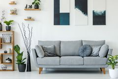 Real photo of a grey couch with pillows standing next to wooden stock photo