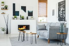 Real photo of a grey couch standing in front of a small wooden t stock photo
