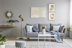 Real photo of a grey sofa with cushions and blanket standing in. Elegant living room interior behind a white table and next to a gold lamp and grey wall with royalty free stock photography
