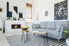 Real photo of a grey sofa standing in front of a wooden table in stock photography