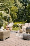 Real photo of a hanging chair and rattan furniture on a wooden t royalty free stock photography
