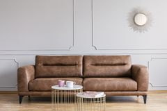 Leather sofa, coffee tables and mirror in a living room interior. Real photo of a leather sofa, coffee tables and mirror in a living room interior royalty free stock photos
