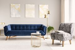 Real photo of a living room interior with a glamour armchair, sofa, paintings, golden lamp and coffee table. Real photo of a living room interior with a glamor royalty free stock photography
