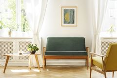 Real photo of a mid-century living room interior with a sofa, co. Ffee table, windows and painting stock images
