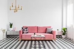 Real photo of a modern living room interior with a checkered flo. Or, pink couch, coffee table and empty, white wall. Place your graphic here royalty free stock image