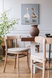 Real photo of a natural daily room interior with chairs, table, clay vase and painting with ducks stock image
