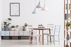 Real photo of a pastel dining room interior with a table, chairs. Cabinets and poster concept royalty free stock photography
