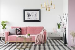 Real photo of a pastel living room interior with a sofa, coffee. Tables, poster, lamp, plants and branches in a vase stock photos