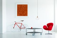 Real photo of a red armchair standing next to a metal table on w. Heels in white living room interior with a painting and a bike royalty free stock photo
