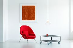 Real photo of a red armchair standing next to a table on wheels stock photo