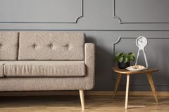 Real photo of a retro sofa standing next to a small table with a Royalty Free Stock Images