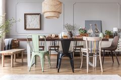 Real photo of a rustical dining room interior with a wicker lamp, table, chairs and plants. Concept royalty free stock photos