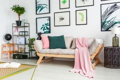 Real photo of a sofa standing next to a wall with paintings and stock photos