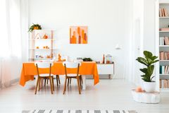 Stylish but simple dining room in vivid color. Orange and white interior design concept. Real photo of stylish but simple dining room in vivid color. Orange and stock photos