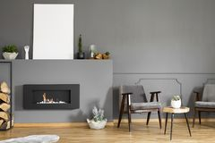 Real photo of two armchairs standing next to a stool and a fireplace with a mockup poster in dark living room interior royalty free stock photos