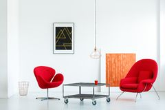 Real photo of two red armchairs standing next to a metal table w. Ith wheels in minimal white living room interior with two posters and a lamp stock images